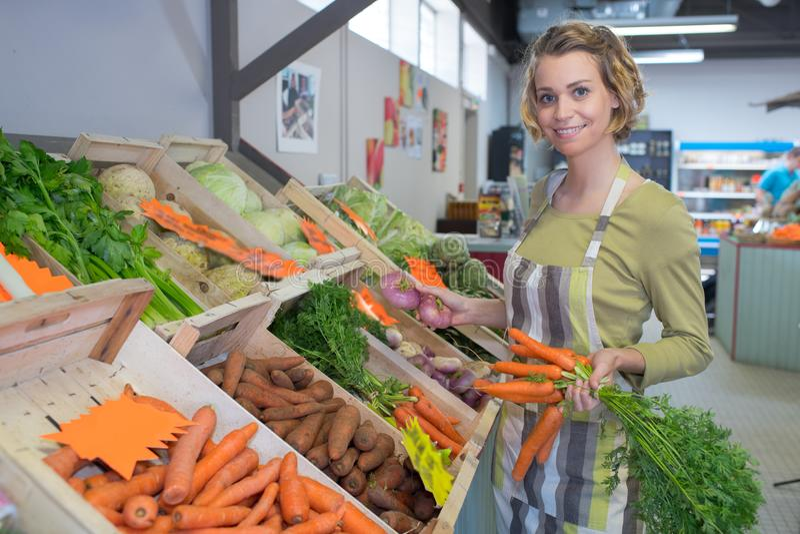 Trabalhador fêmea que vende frutas e legumes frescas no mercado foto de stock royalty free