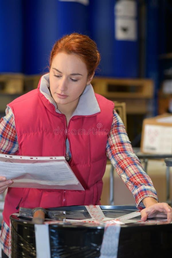 Trabalhador fêmea que verifica o pacote contra o documento fotografia de stock