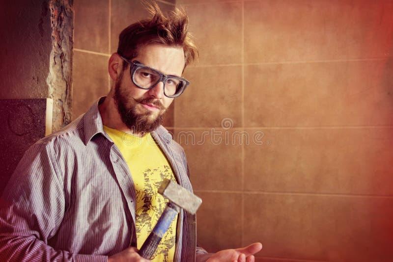 Trabalhador farpado áspero nos óculos de proteção que batem o martelo na palma com a intenção da espuma alguém pescoço ou para de foto de stock royalty free