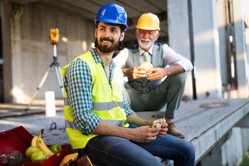 Trabalhador feliz novo e do engenheiro chefe que senta-se no terreno de construção na ruptura fotos de stock royalty free