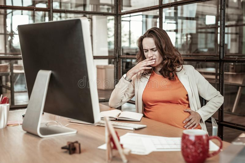 Trabalhador grávido afligido que tem problemas da digestão e náusea da gravidez fotografia de stock
