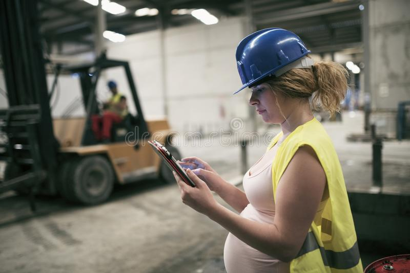 Trabalhador grávido na fábrica com tabuleta fotos de stock