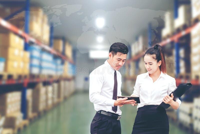 Trabalhador homem de negócio e de mulher asiáticos do negócio na utilização do armazém fotos de stock