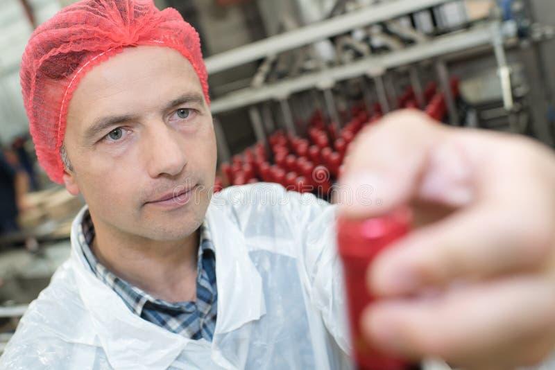 Trabalhador industrial adulto meados de que olha a garrafa na fábrica foto de stock royalty free