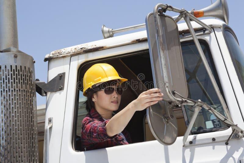 Trabalhador industrial fêmea asiático que ajusta o espelho ao sentar-se no caminhão de registo fotos de stock royalty free