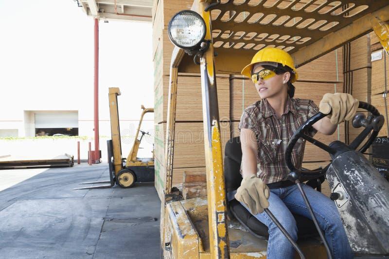 Trabalhador industrial fêmea que olha ausente ao conduzir o caminhão de empilhadeira imagens de stock