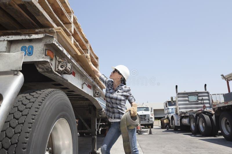 Trabalhador industrial fêmea que prende com correias abaixo das pranchas de madeira no caminhão de registro foto de stock royalty free