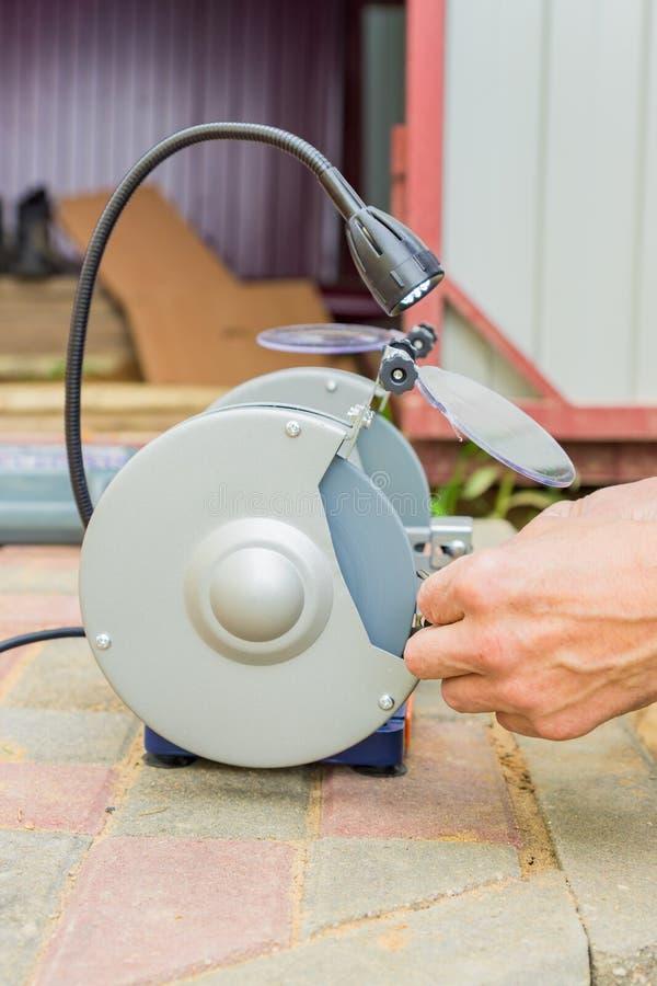 Trabalhador industrial que aponta a broca com a máquina abrasiva do cortador do disco da mó fora foto de stock royalty free