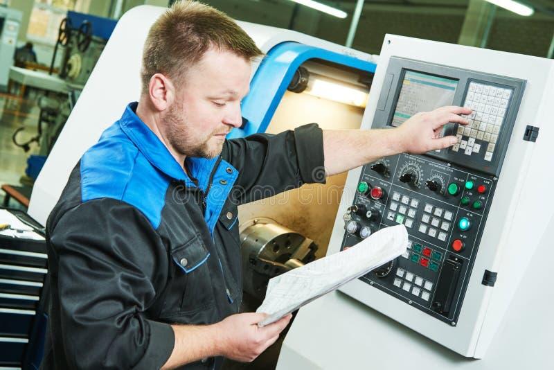 Trabalhador industrial que opera a máquina de giro do cnc na indústria fazendo à máquina do metal fotografia de stock