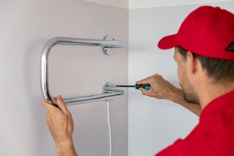 Trabalhador instalando secador elétrico de toalha na parede do banheiro imagem de stock