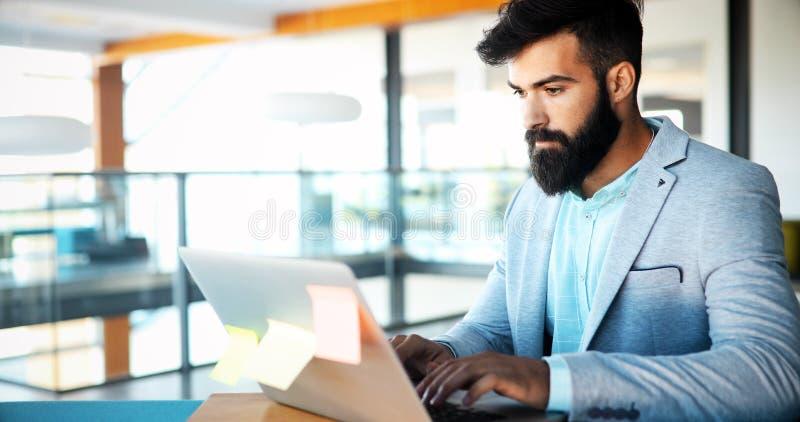 Trabalhador jovem no computador durante o dia de trabalho no escritório fotografia de stock