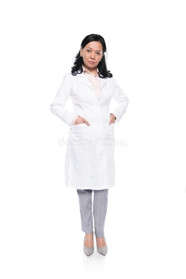 Trabalhador médico profissional sério no revestimento branco que está com mãos em uns bolsos fotos de stock