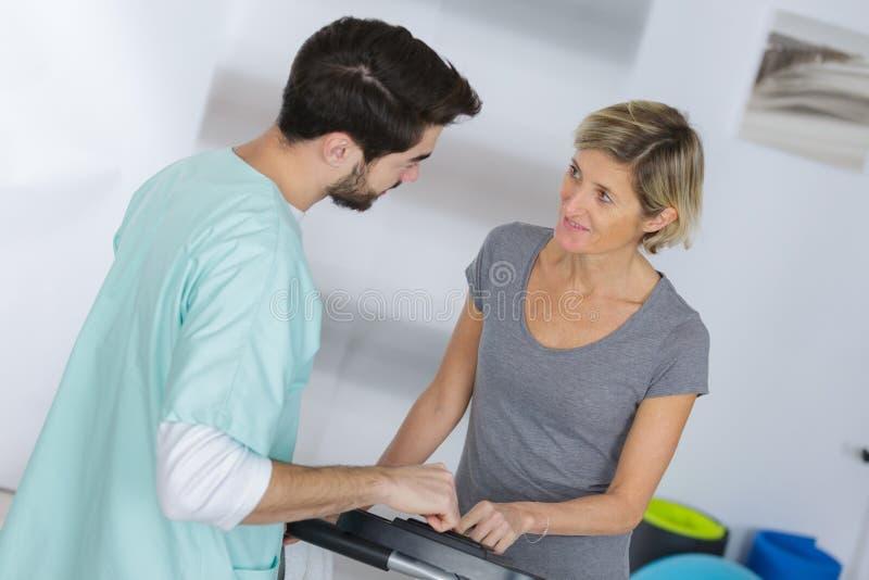 Trabalhador médico que comunica-se com a mulher envelhecida meio imagem de stock royalty free