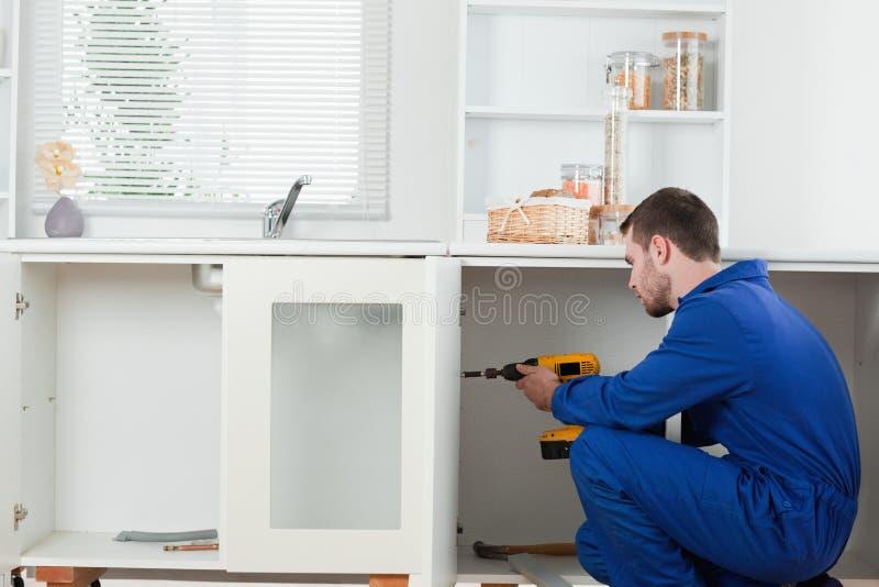 Trabalhador manual bonito que fixa uma porta imagem de stock