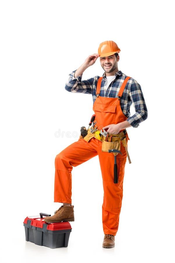 Trabalhador manual de sorriso no macacão alaranjado e no capacete de segurança que inclinam-se na caixa de ferramentas foto de stock