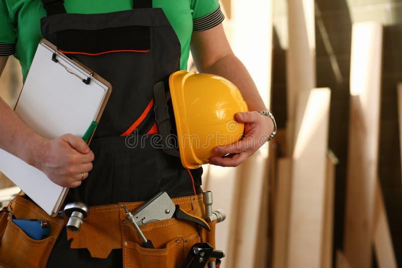 Trabalhador manual desconhecido com mãos na correia da cintura e da ferramenta com as ferramentas da construção contra o fundo ci foto de stock