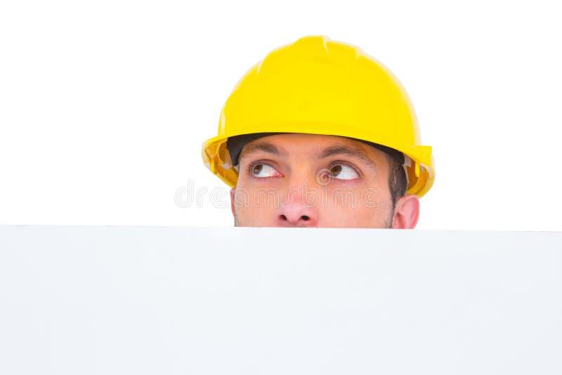 Trabalhador manual escondido atrás da placa vazia fotografia de stock royalty free
