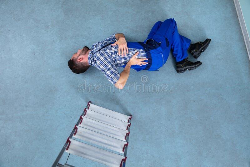 Trabalhador manual ferido Lying On Floor foto de stock
