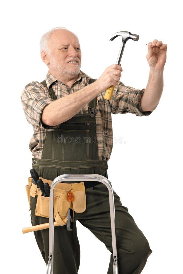 Trabalhador manual idoso que martela o prego fotos de stock