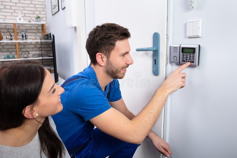Trabalhador manual Installing Security System perto da parede da porta fotos de stock