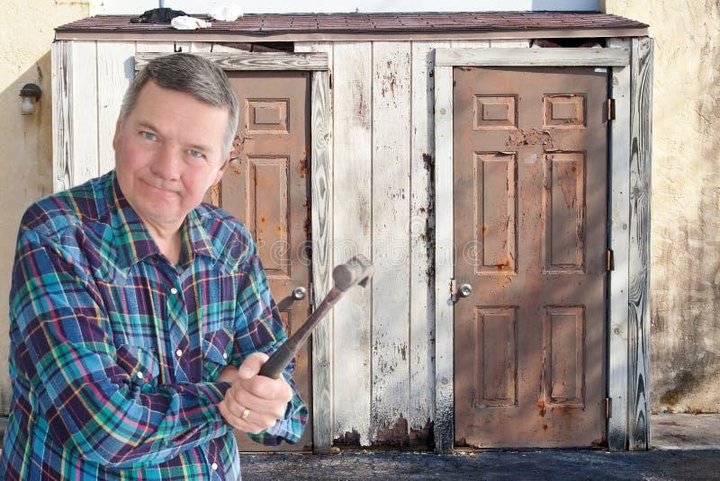 Trabalhador manual maduro com o martelo que começ pronto para rasgar fotografia de stock royalty free