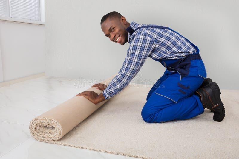 Trabalhador manual masculino Rolling Carpet imagem de stock