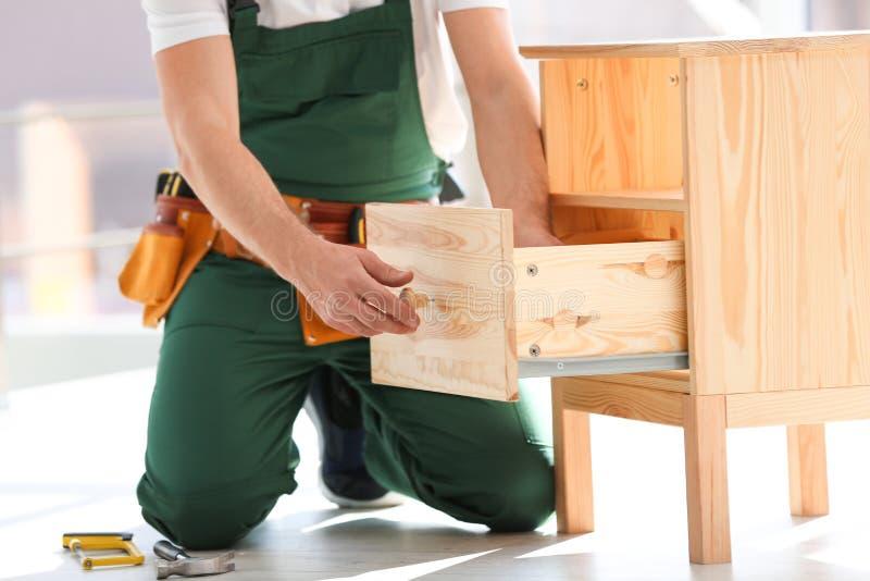 Trabalhador manual na mobília de montagem uniforme dentro, close up imagens de stock royalty free