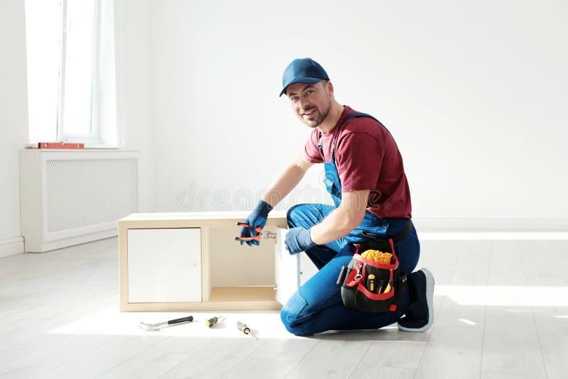 Trabalhador manual na mobília de montagem uniforme dentro fotos de stock