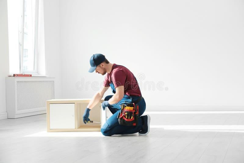 Trabalhador manual na mobília de montagem uniforme dentro Ferramentas profissionais da constru??o imagens de stock