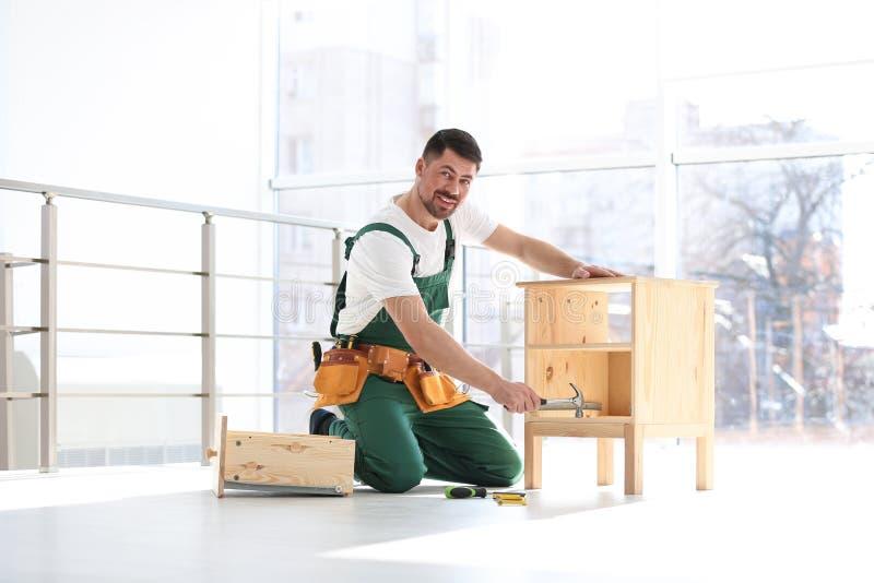 Trabalhador manual na mobília de montagem uniforme Ferramentas profissionais da constru??o foto de stock