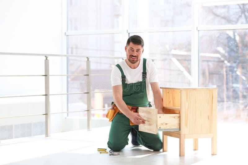 Trabalhador manual na mobília de montagem uniforme Ferramentas profissionais da constru??o fotografia de stock