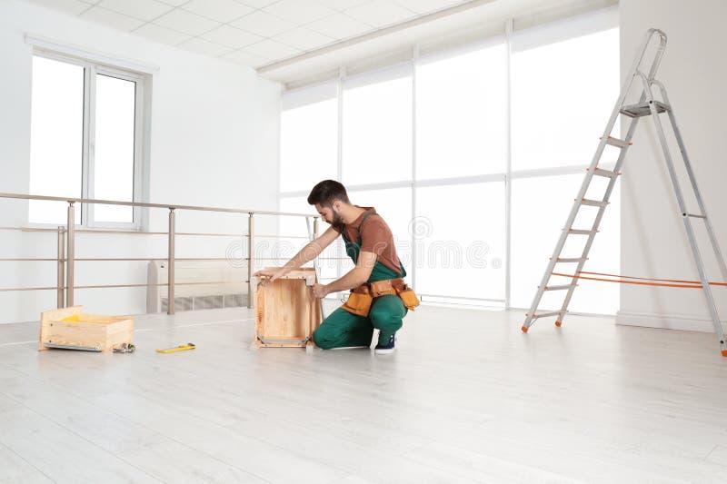 Trabalhador manual na mobília de montagem uniforme Ferramentas profissionais da constru??o imagens de stock