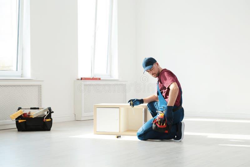 Trabalhador manual na mobília de montagem uniforme Ferramentas profissionais da constru??o fotografia de stock royalty free