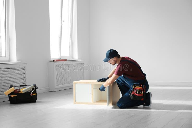Trabalhador manual na mobília de montagem uniforme Ferramentas profissionais da constru??o imagem de stock royalty free
