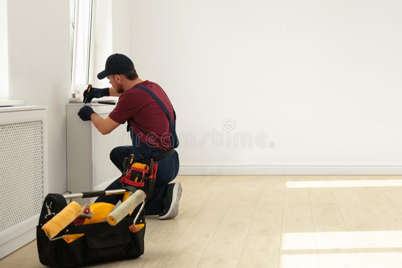 Trabalhador manual no funcionamento do uniforme com chave de fenda dentro Ferramentas profissionais da constru??o imagens de stock