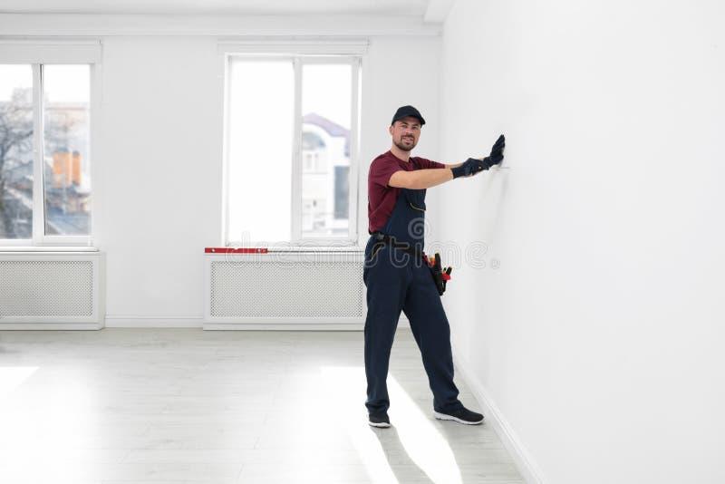 Trabalhador manual no funcionamento do uniforme com chave de fenda dentro Ferramentas profissionais da constru??o imagem de stock