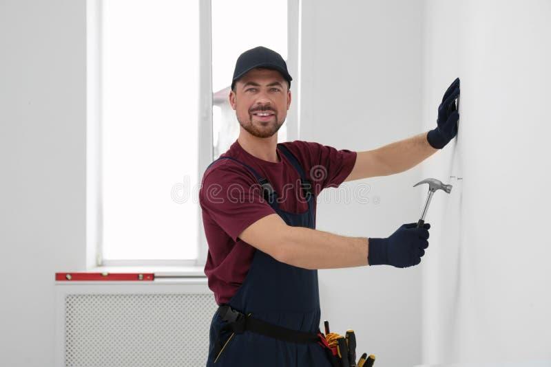Trabalhador manual no funcionamento do uniforme com martelo Ferramentas profissionais da constru??o imagens de stock royalty free