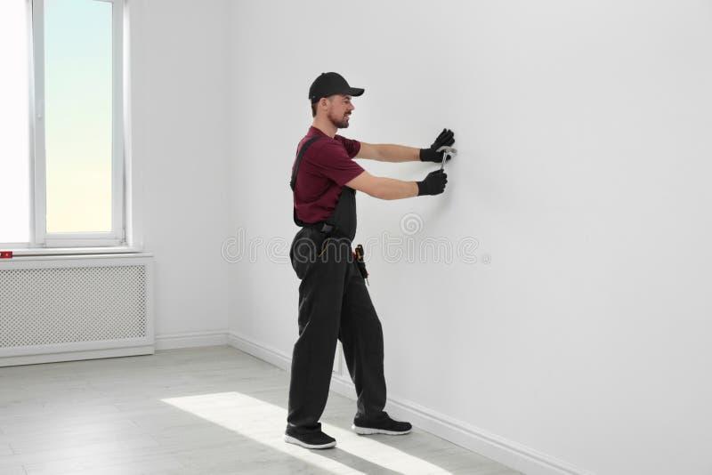 Trabalhador manual no funcionamento do uniforme com martelo Ferramentas profissionais da constru??o imagens de stock