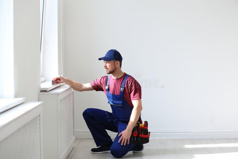 Trabalhador manual no funcionamento do uniforme com nível da construção dentro fotos de stock