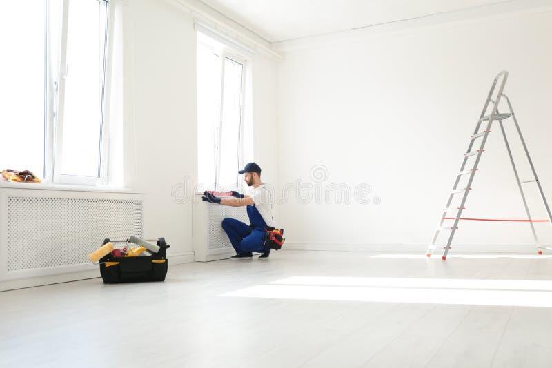 Trabalhador manual no funcionamento do uniforme com nível da construção dentro Ferramentas profissionais da constru??o imagens de stock