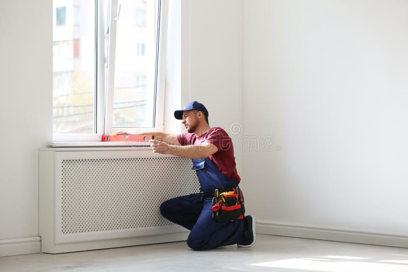 Trabalhador manual no funcionamento do uniforme com nível da construção Ferramentas profissionais da constru??o fotos de stock royalty free