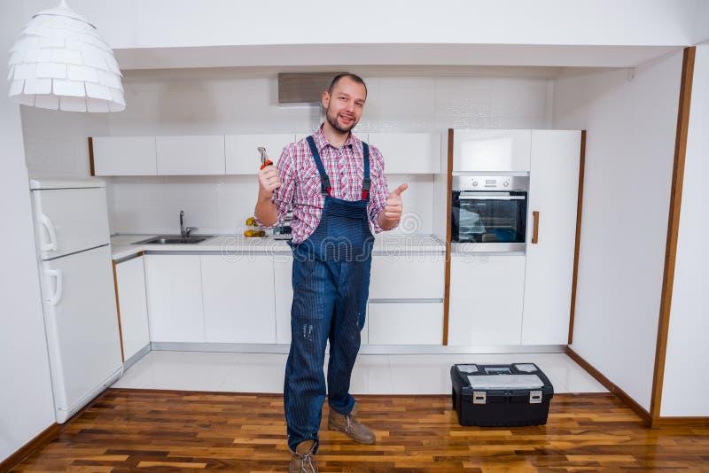 Trabalhador manual no uniforme que está ao lado da caixa de ferramentas na cozinha imagem de stock royalty free