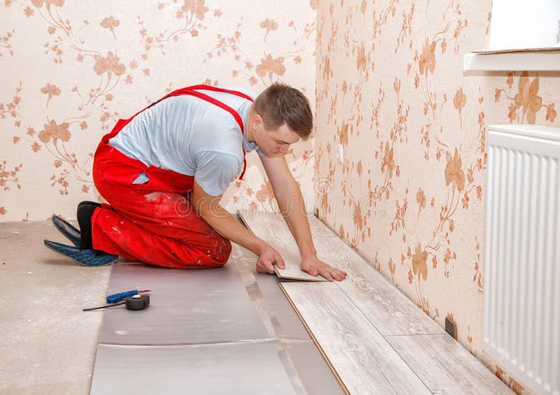 Trabalhador manual novo que instala o assoalho de madeira fotografia de stock