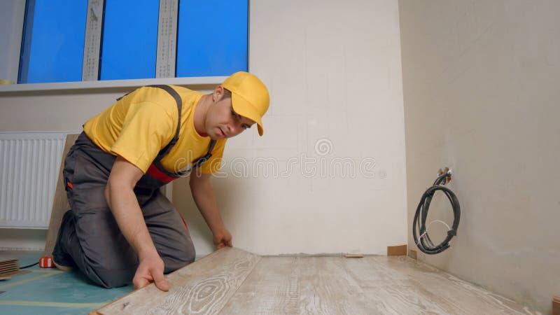 Trabalhador manual novo que instala o assoalho de madeira na casa nova imagem de stock royalty free