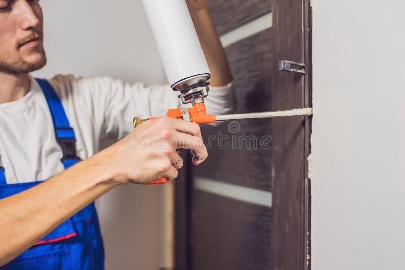 Trabalhador manual novo que instala a porta com uma espuma da montagem em uma sala fotografia de stock