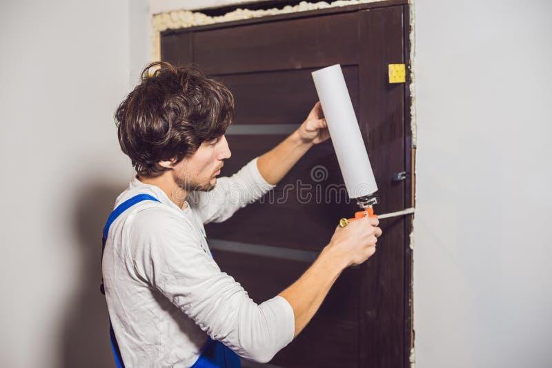 Trabalhador manual novo que instala a porta com uma espuma da montagem em uma sala imagem de stock royalty free