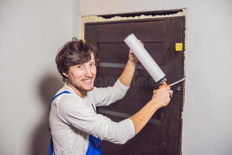 Trabalhador manual novo que instala a porta com uma espuma da montagem em uma sala fotos de stock