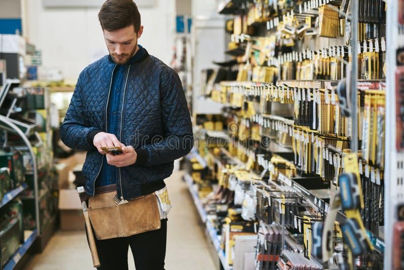 Trabalhador manual novo que verifica a informação em seu móbil foto de stock royalty free
