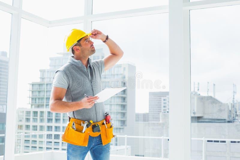Trabalhador manual que inspeciona a construção imagem de stock