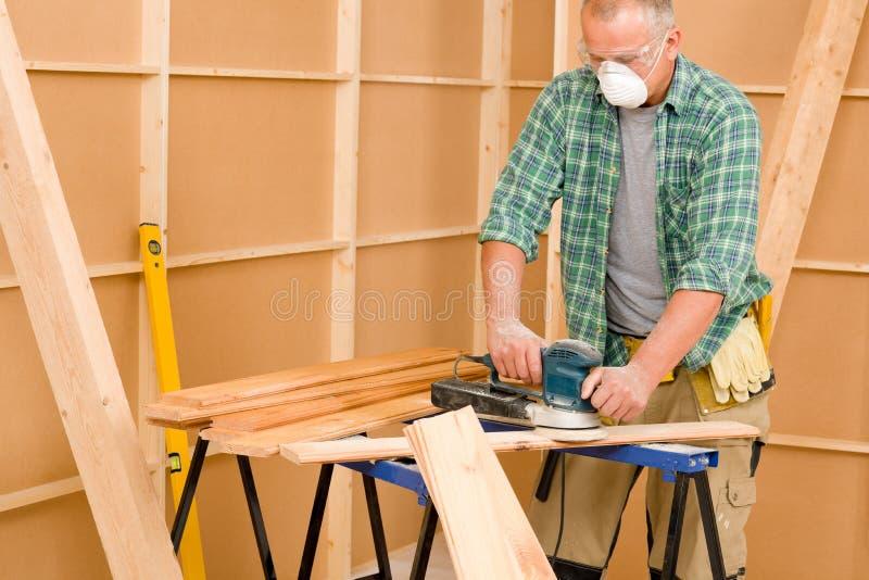 Trabalhador manual que lixa a renovação home diy da placa de madeira imagem de stock royalty free